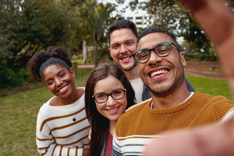 Multi ethnic people enjoying time together and taking selfie in the park royalty free stock photos