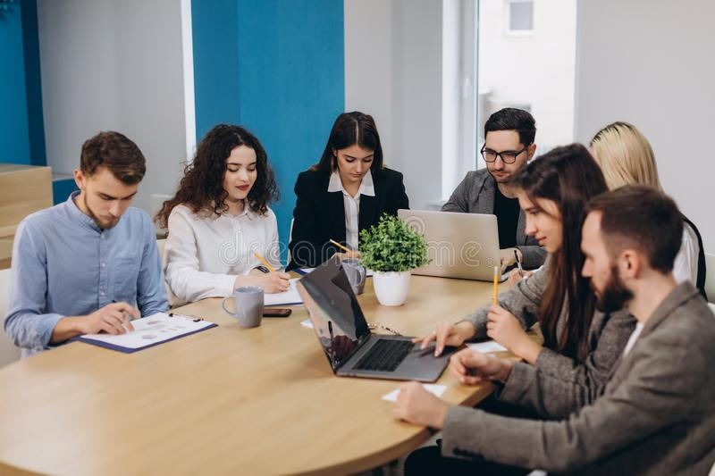 Multi ethnic people entrepreneur, small business concept. Woman showing coworkers something on laptop computer as they gather. Around a conference table royalty free stock photo