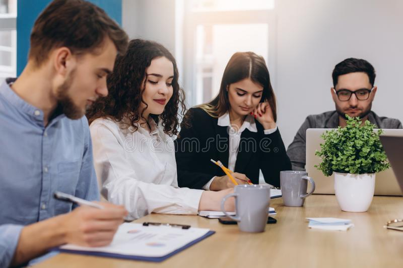 Multi ethnic people entrepreneur, small business concept. Woman showing coworkers something on laptop computer as they gather stock photo