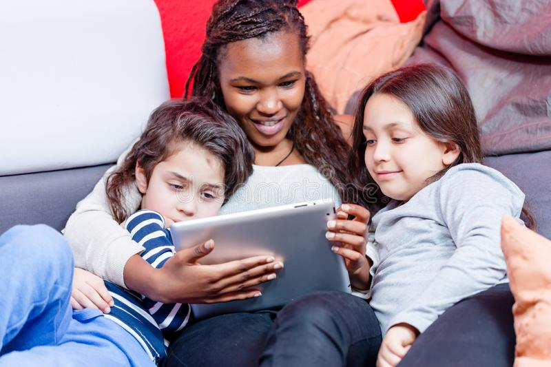 Multi ethnic sibling watching videos royalty free stock photography