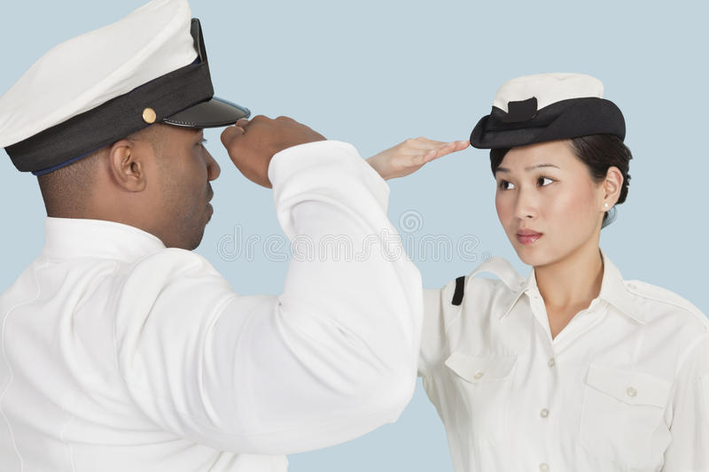 Multi-ethnic US Navy officers saluting each other over light blue background stock image