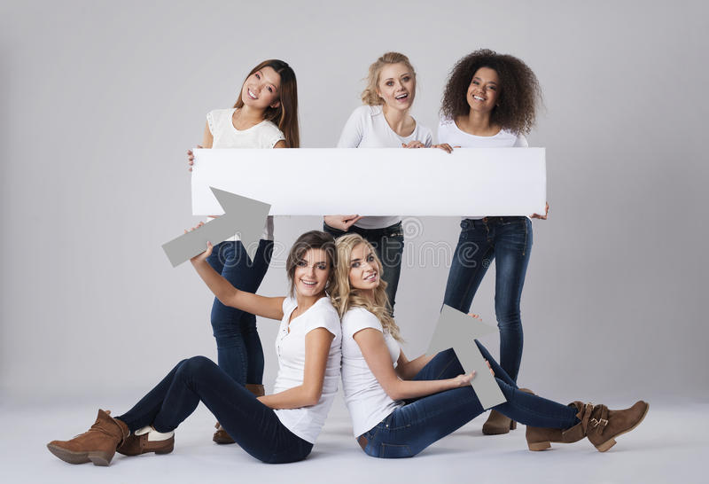 Multi ethnic women with empty board stock photography