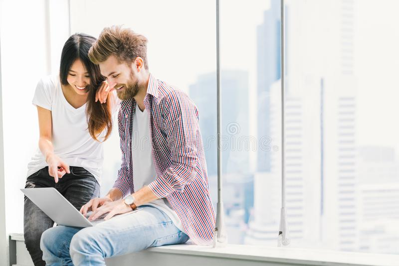 Multi-ethnic young couple or college student using notebook laptop together in campus or office. Information technology concept royalty free stock images