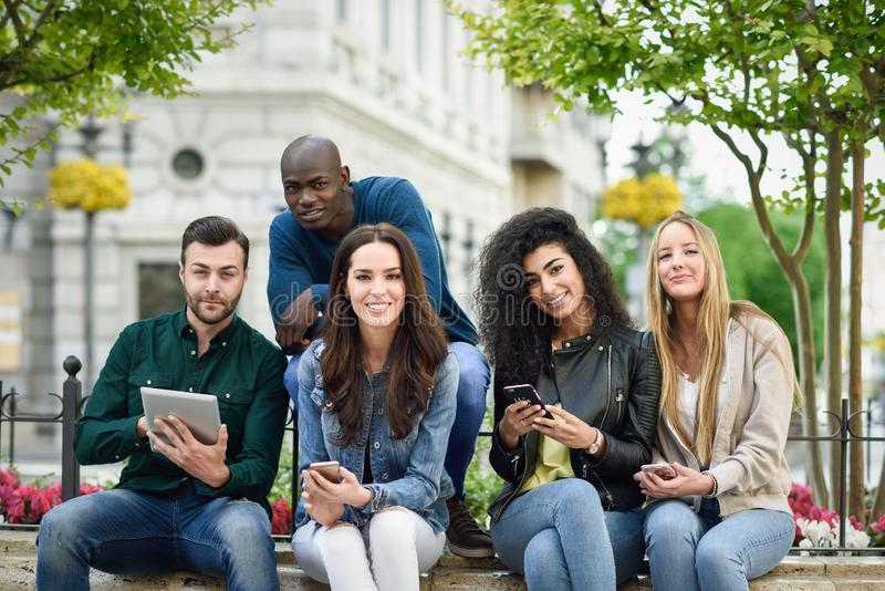 Multi-ethnic young people using smartphone and tablet computers royalty free stock images