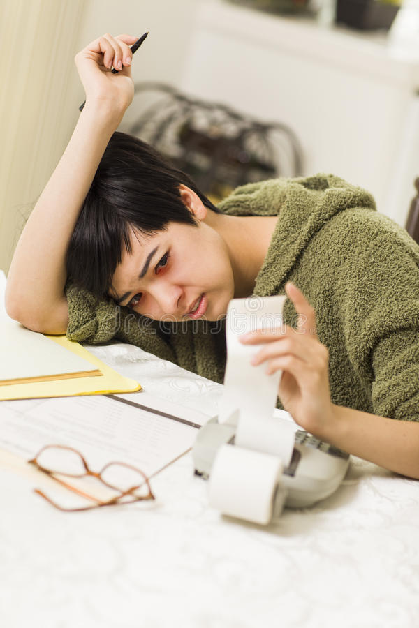 Multi-ethnic Young Woman Agonizing Over Financial Calculations stock photography