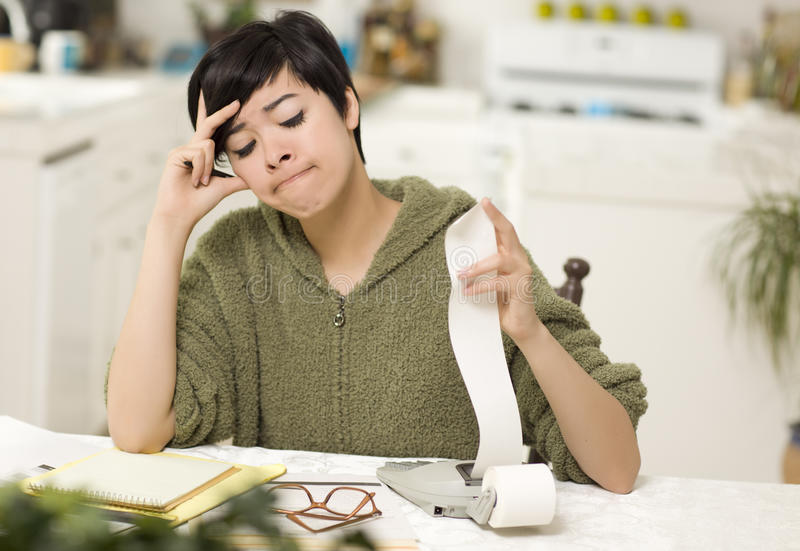 Multi-ethnic Young Woman Agonizing Over Financial Calculations royalty free stock image