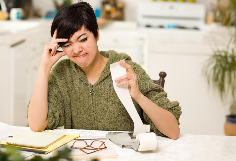 Multi-ethnic Young Woman Agonizing Over Financials stock image