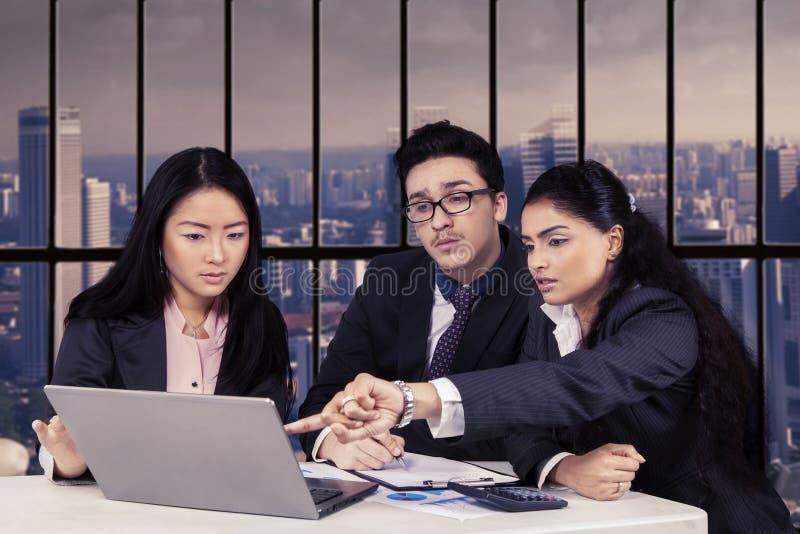 Multi ethnische Angestellte, die im Büro sich besprechen lizenzfreies stockbild