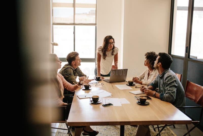 Multi ethnische Geschäftsleute, die eine Sitzung im Büro haben stockbild