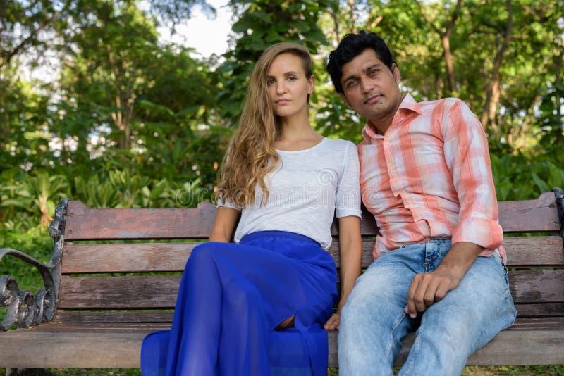 Multi ethnische Paare, die auf Holzbank in der Liebe an ruhigem sitzen lizenzfreies stockbild