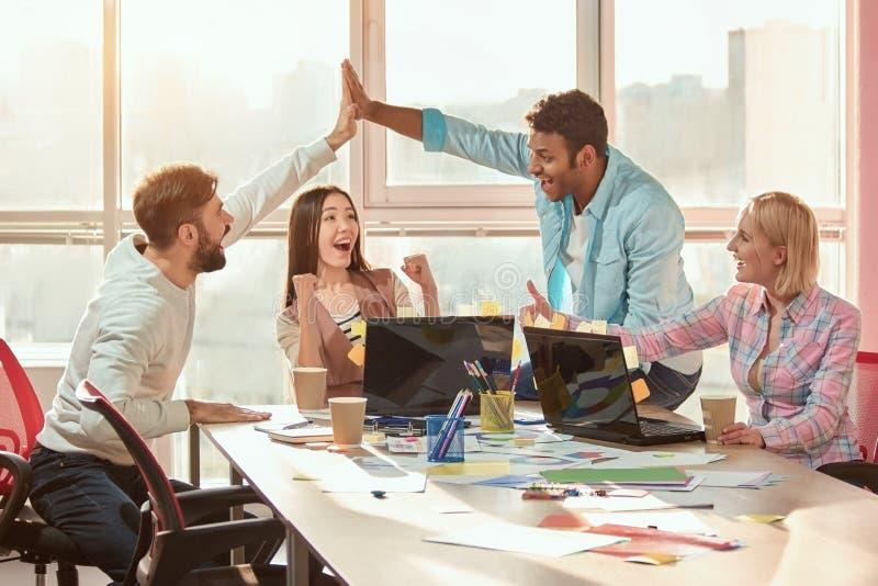 Multi ethnisches Team von Geschäftsleuten Designern, die Erfolg sich freuen lizenzfreies stockfoto
