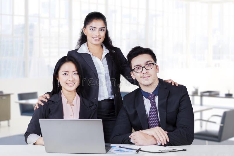 Multi etnisch commercieel drie team die in bureau glimlachen stock afbeelding