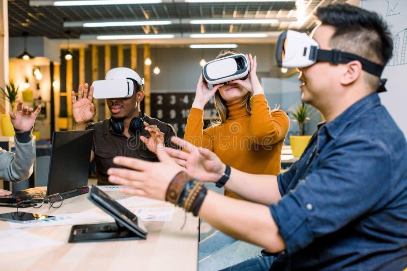 Multi-etnisch Commercieel team die virtuele werkelijkheidshoofdtelefoon in bureauvergadering met behulp van Jonge ontwikkelaars d stock foto's