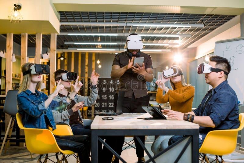 Multi-etnisch Commercieel team die virtuele werkelijkheidshoofdtelefoon in bureauvergadering met behulp van Jonge ontwikkelaars d royalty-vrije stock fotografie