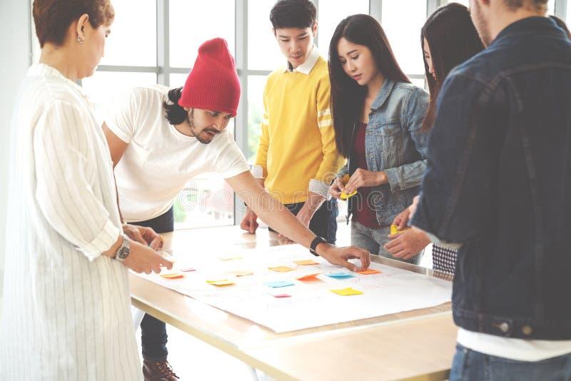 Multi-etnisch creatief team die, en brainstorming op lijst in werkplaats samenkomen samenwerken De uitwisseling van ideeën van he royalty-vrije stock foto's