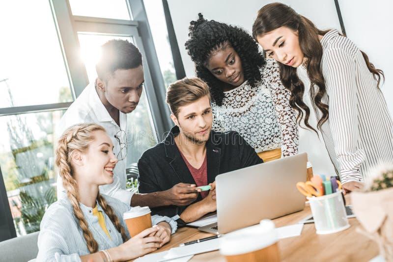multi-etnisch geconcentreerd commercieel team die aan laptop op het werk samenwerken stock foto's