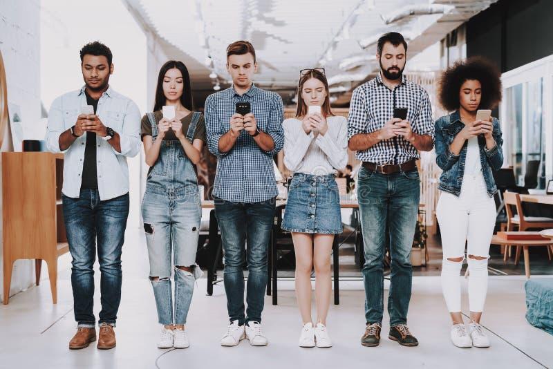 Multi-etnisch Jonge mensen Tribune in lijn mobile royalty-vrije stock foto's