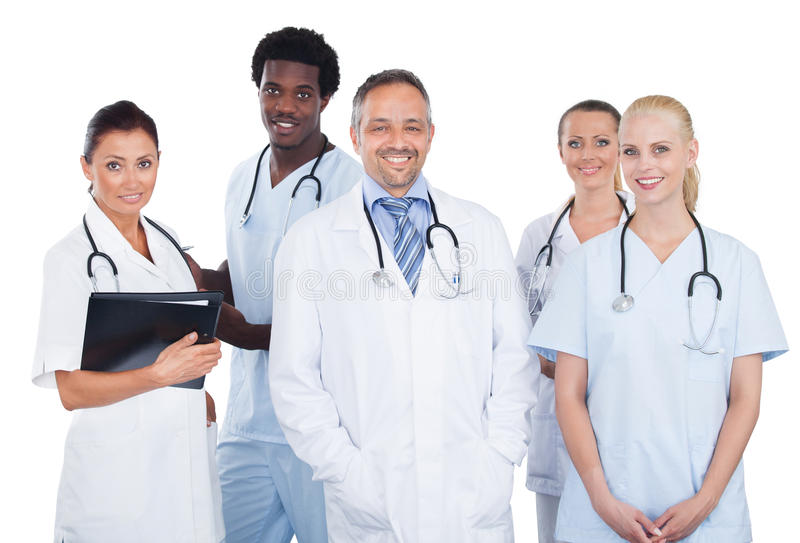 Multi-etnisch medisch team die zich over witte achtergrond bevinden royalty-vrije stock afbeeldingen