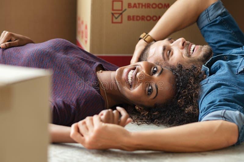 Multi-etnisch paar die op vloer na het bewegen van huis liggen stock foto's