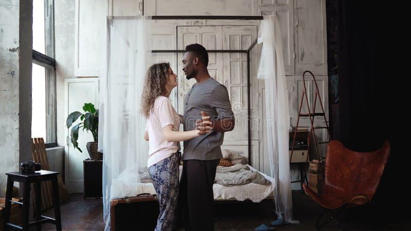 Multi-etnisch paar die in pyjama's dansen Het Afrikaanse mannelijke en Kaukasische wijfje kijkt gelukkig, het lachen en het gliml royalty-vrije stock afbeeldingen