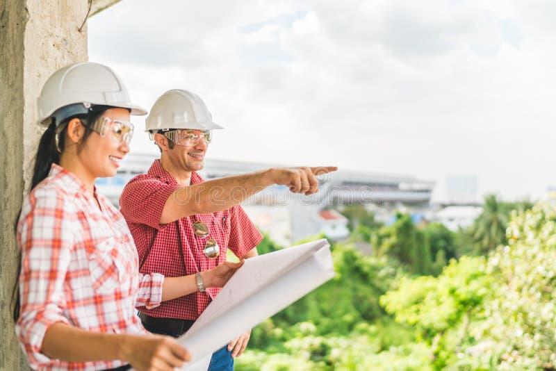 Multi-etnisch paar van bouwingenieurs die samen met blauwdruk bij bouwterrein werken royalty-vrije stock afbeeldingen