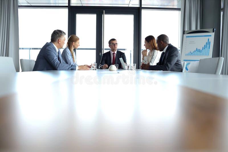 Multi-etnische bedrijfsmensen die bespreking hebben bij conferentielijst in bureau royalty-vrije stock afbeeldingen