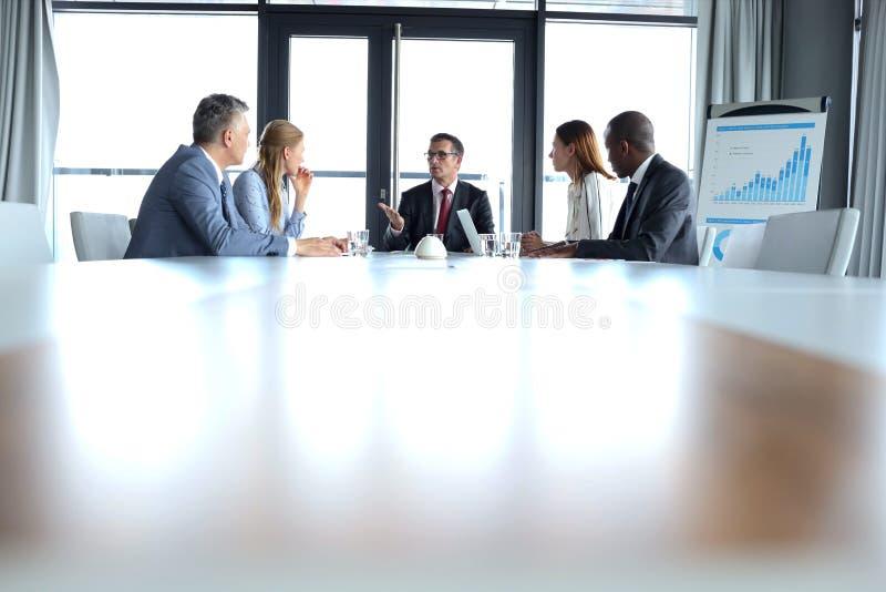 Multi-etnische bedrijfsmensen die bespreking hebben bij lijst in raadsruimte stock fotografie