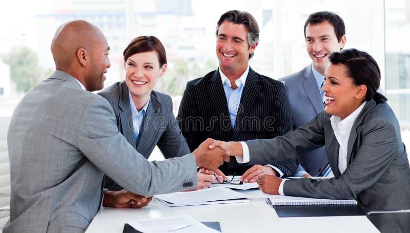 Multi-etnische bedrijfsmensen die elkaar begroeten stock afbeelding
