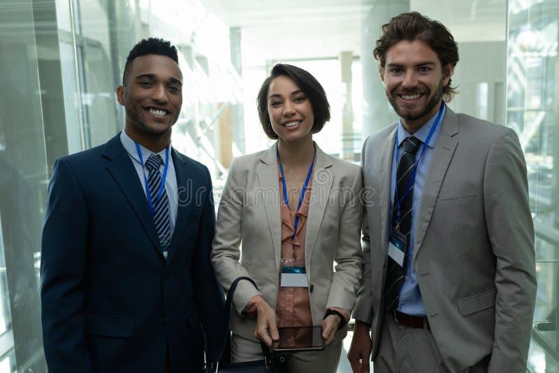 Multi-etnische bedrijfsmensen die en zich camera in bureaulift bevinden bekijken royalty-vrije stock fotografie