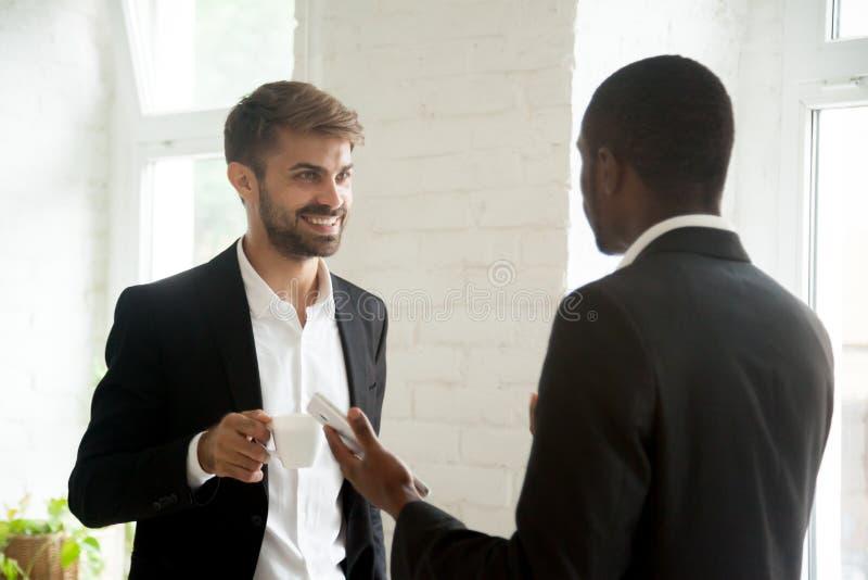 Multi-etnische collega's die bedrijfsgesprek hebben tijdens coffe stock afbeelding