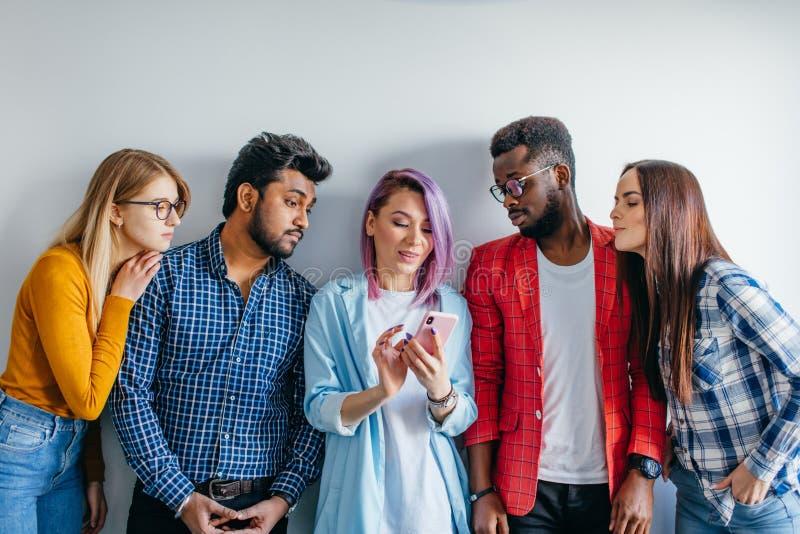 Multi-etnische die Groep Jongeren in Vrijetijdskleding over grijze achtergrond wordt geïsoleerd stock afbeelding