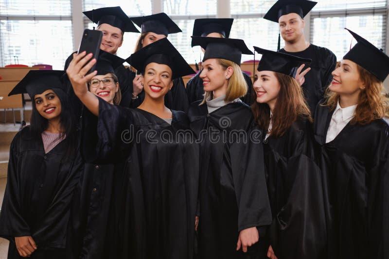 Multi etnische groep gediplomeerde studenten die selfie nemen royalty-vrije stock foto's