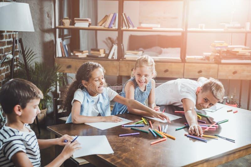 multi-etnische groep gelukkige kinderen die beelden zich samentrekken stock afbeelding