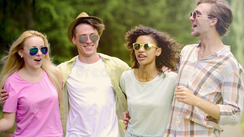 Multi-etnische groep vrienden die pret hebben en in park, vakantie, het samenkomen ontspannen stock foto