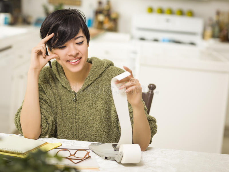 Multi-etnische Jonge Vrouw die over Financiële Berekeningen glimlachen stock foto's