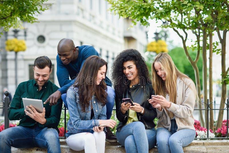 Multi-etnische jongeren die smartphone en tabletcomputers met behulp van stock afbeeldingen