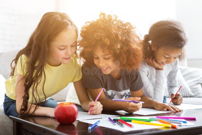 Multi-etnische meisjes die bij lijst met kleurrijke potloden trekken stock fotografie