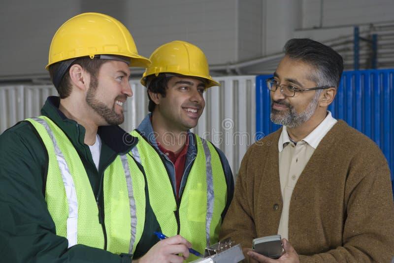 Multi-etnische Mensen die in Fabriek bespreken stock foto