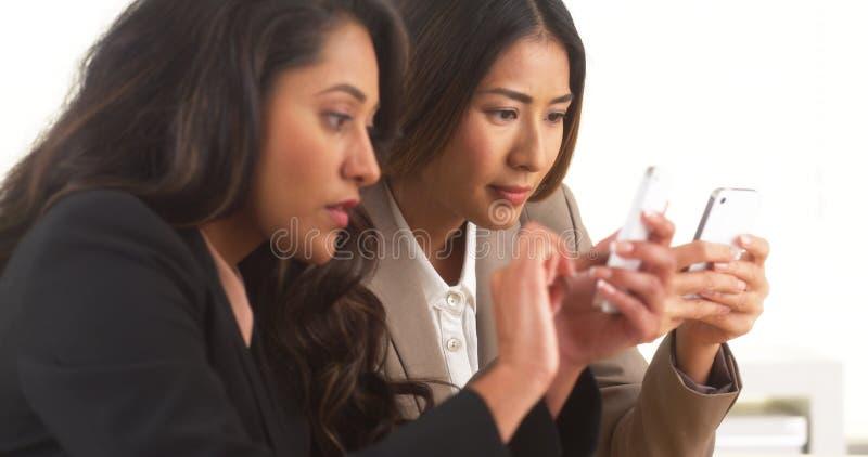 Multi-etnische onderneemsters die aan smartphones werken stock foto's