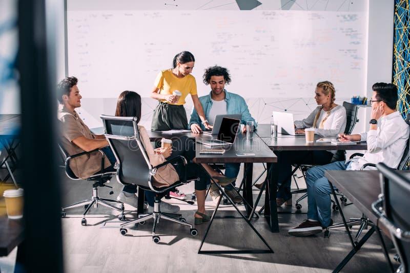 multi-etnische partners die vergadering hebben bij lijst met laptops in modern stock afbeelding