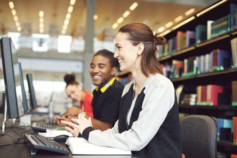 Multi-etnische studenten die computers voor het vinden van informatie voor hun studie met behulp van stock fotografie