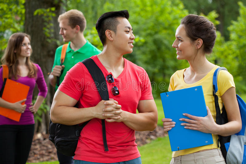 Multi-etnische studenten met omslagen en rugzakken stock afbeeldingen