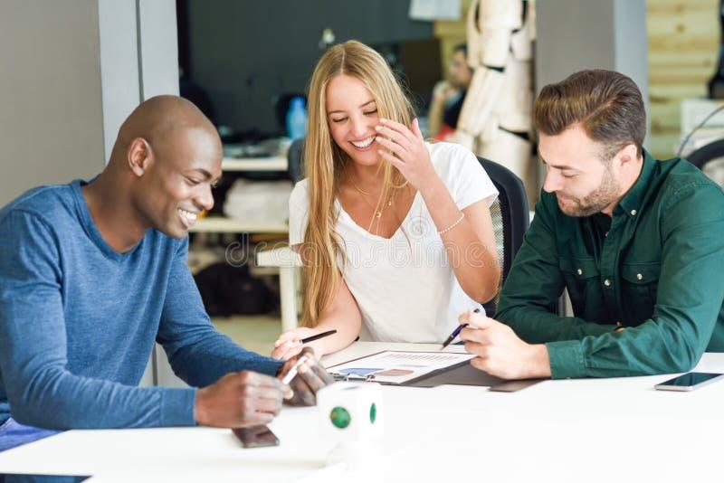 Multi-etnische triojongeren die en bestuderen glimlachen aan stock foto's