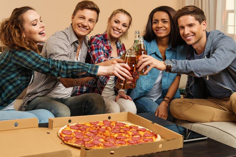 Multi-etnische vrienden die in huisbinnenland vieren stock foto's