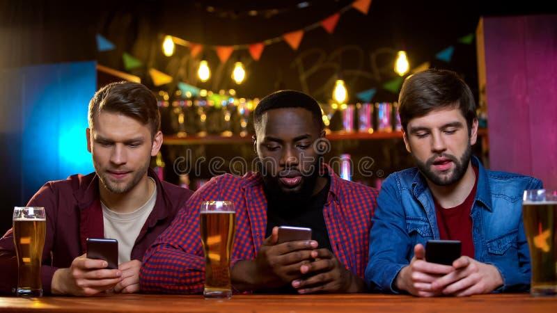 Multi-etnische vrienden die smartphones zitting in bar, probleem met mededeling gebruiken royalty-vrije stock foto's