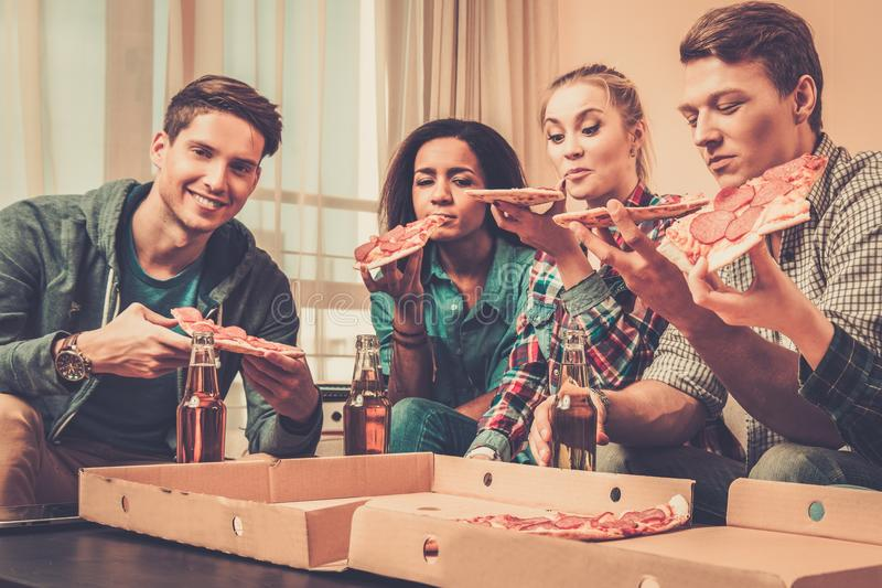 Multi-etnische vrienden met pizza en flessen van dranken royalty-vrije stock afbeeldingen