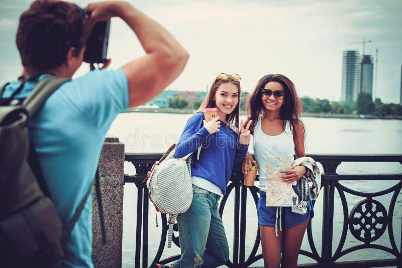 Multi-etnische vriendentoeristen die foto nemen dichtbij rivier in een stad stock afbeeldingen