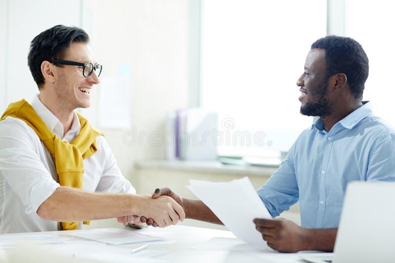 Multi-etnische werknemers die overeenkomst in bureau besluiten stock afbeelding