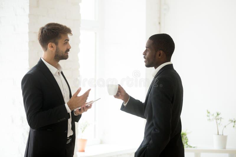 Multi-etnische zakenlieden die bedrijfsstrategieën bespreken tijdens wo stock foto