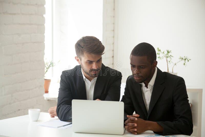 Multi-etnische zakenlieden die bij laptop samenwerken stock afbeeldingen